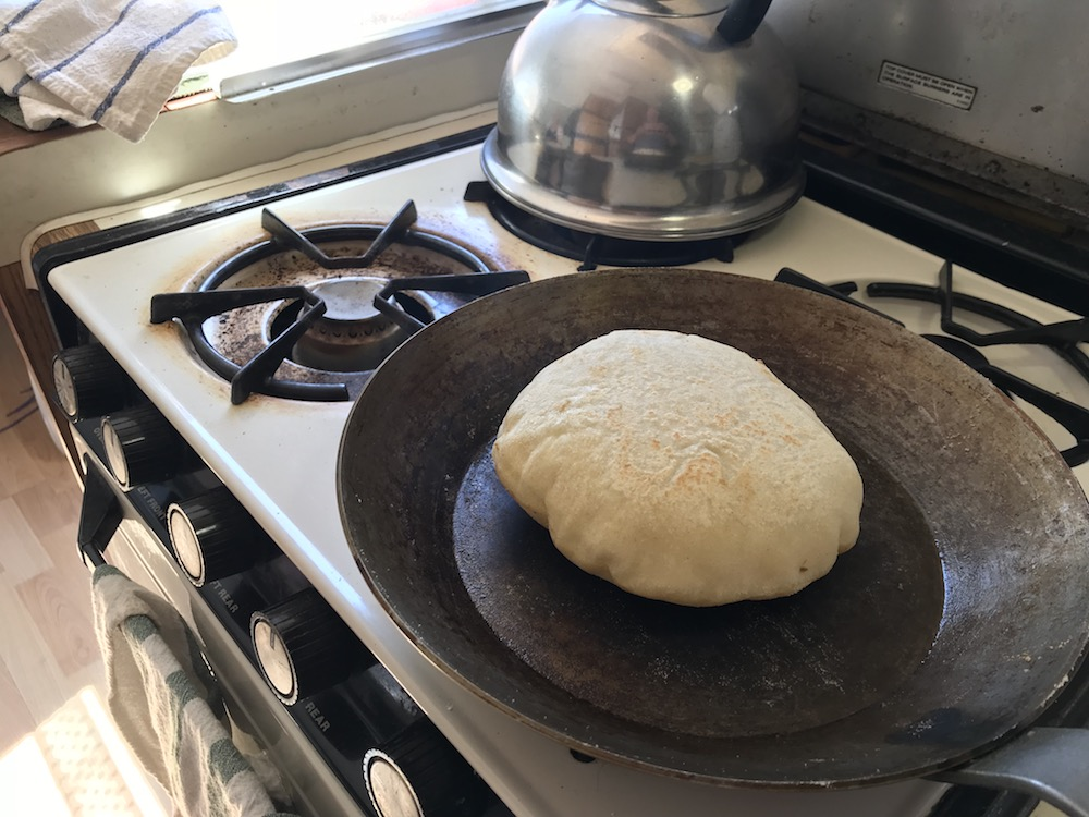 Perfectly puffed pita bread in the carbon steel pan on the stovetop. Yum!